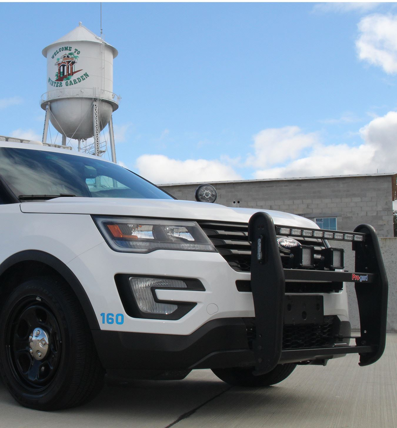 Police Vehicle Parked in Front of Water Tower